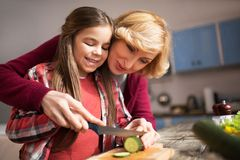 Grandmother and cute granddaughter cooking salad. Grandmother showing little girl how to cut cucumber. Family holiday concept Royalty Free Stock Photos
