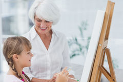 Grandmother and cute granddaughter painting together Stock Photography