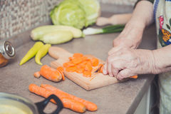 Grandmother cutting vegetables stock image