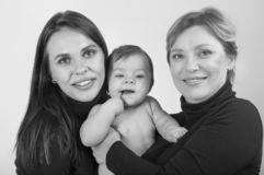 Grandmother, daughter and granddaughter on white portrait, happy family concept. Black and white stock image