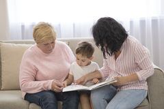 Grandmother and daughter reading a tale to her grandson. Family Reading Leisure stock images
