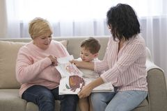 Grandmother and daughter reading a tale to her grandson. Family Reading Leisure stock photo