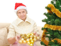 Grandmother decorates the Christmas tree Stock Photo