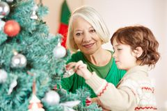 Grandmother decorating christmas tree with grandchild. Grandmother decorating christmas tree together with her grandchild royalty free stock image