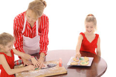 Grandmother decorating cookies with children. Isolated on white Royalty Free Stock Photo