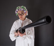 Grandmother in defence. Beautiful grandmother posing with weapon in studio. Serious lady with rollers on looking at camera and holding rifle Stock Photos