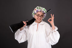 Grandmother in defence. Happy grandmother posing in studio over grey background. Pretty woman in glasses in defence giving okay sign in studio Royalty Free Stock Photo
