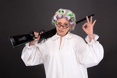 Grandmother in defence. Grandmother holding rifle and showing okay sign in studio over grey background. Happy elderly in glasses defending her residence Royalty Free Stock Photography