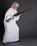 Grandmother in defence. Grandmother with rollers on protecting her house from robberies. Beautiful elderly defending her apartment with rifle. Studio shot Stock Photography