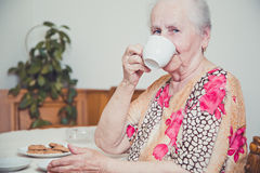Grandmother drinking a cup of tea. In her house Royalty Free Stock Image