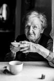 Grandmother drinking tea. Black-and-white portrait of woman. Grandmother drinking tea. Black-and-white portrait of an elderly woman Stock Images