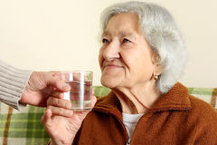 Grandmother drinks a glass water royalty free stock photos
