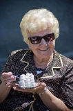Grandmother eating cake. Outdoor portrait of a smiling grandmother eating a sweet cake Stock Photography