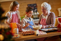Grandmother enjoying with children making Christmas cookies. At home stock photo