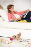 Grandmother enjoying a rest on sofa Stock Images