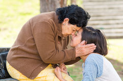 Grandmother facing granddaughter touching heads outdoors, lovely picture displaying love between people Royalty Free Stock Image