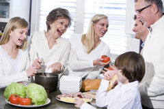 Grandmother with family laughing in kitchen royalty free stock photography