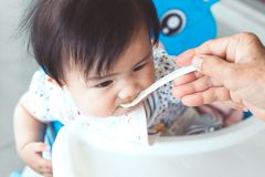 Grandmother feeding cute asian baby girl with a spoon Royalty Free Stock Images