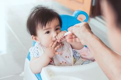 Grandmother feeding cute asian baby girl with a spoon Stock Photo