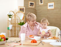 Grandmother Feeding Granddaughter At Home Stock Images