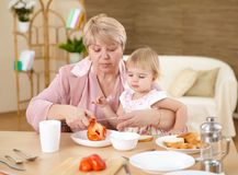 Grandmother feeding granddaughter at home Royalty Free Stock Photography