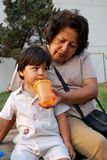 Grandmother feeding her grandson water Royalty Free Stock Photos