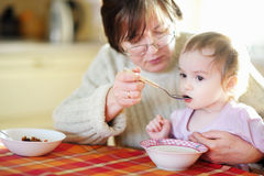 Grandmother feeding her little baby granddaughter Stock Photos