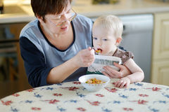 Grandmother feeding her little baby granddaughter Royalty Free Stock Images