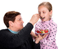 Grandmother feeds strawberry pie to her granddaughter Stock Image