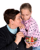 Grandmother feeds strawberry to her granddaughter Stock Photos