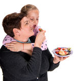 Grandmother feeds strawberry to her granddaughter Royalty Free Stock Photo