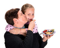 Grandmother feeds strawberry to her granddaughter Stock Image