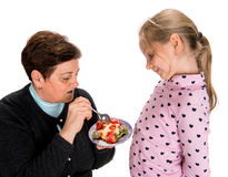 Grandmother feeds strawberrypie to her granddaughter Stock Photography