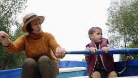 Grandmother floating on blue wooden boat with grandchild on lake in park. Happy family on boat in park. Granny and grandson talkin. G and sitting on wooden boat stock footage