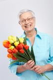 Grandmother with flowers smiling. Grandmother holding bouquet of flowers, smiling Stock Image