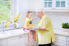 Grandmother and funny girl baking pie in white kitchen. Happy beautiful great grandmother and her adorable granddaughter, curly toddler girl in colorful dress Royalty Free Stock Images