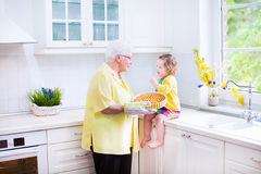 Grandmother and funny girl baking pie in white kitchen. Happy beautiful great grandmother and her adorable granddaughter, curly toddler girl in colorful dress Royalty Free Stock Photo