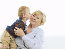 Grandmother getting a kiss from grandson. Isolated on white background Royalty Free Stock Images