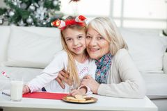 Grandmother And Girl Smiling During Christmas Stock Photo
