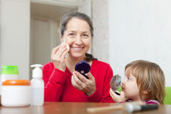 Grandmother with gitl puts facepowder. Happy grandmother with granddaughter puts facepowder on face Royalty Free Stock Photo