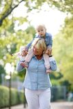 Grandmother giving piggyback to cute back Stock Image