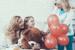 Grandmother Giving Toy Bear to Happy Girl at Home stock image