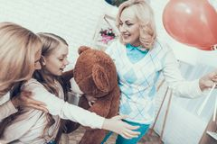 Grandmother Giving Toy Bear to Happy Girl at Home royalty free stock photo