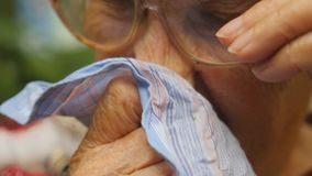 Grandmother in glasses blowing her nose into handkerchief outdoor. Portrait of a sick old woman. Close up Slow motion stock video