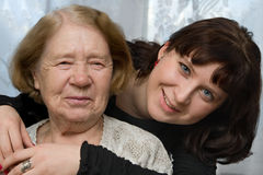 The grandmother and the grand daughter. The grand daughter embraces the grandmother Stock Images