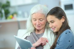 Grandmother and grand daughter watching tablet royalty free stock photo