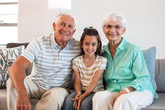 Grandmother and grand father with their granddaughter. Portrait of Grandmother and grand father with their granddaughter sitting on sofa in living room stock photography