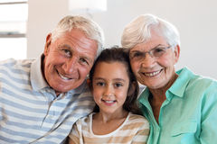 Grandmother and grand father with their granddaughter. Portrait of Grandmother and grand father with their granddaughter sitting on sofa in living room royalty free stock images