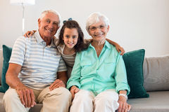 Grandmother and grand father with their granddaughter. Portrait of grandmother and grand father with their granddaughter sitting on sofa in living room royalty free stock image