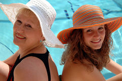 Grandmother and Grandaughter. A grandmother and grandaughter share a day at the pool in sun hats Stock Photo